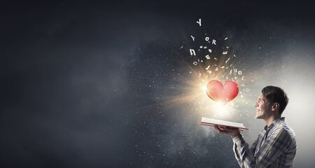 Young man with opened book in hands and red heart on pages Stock Photo