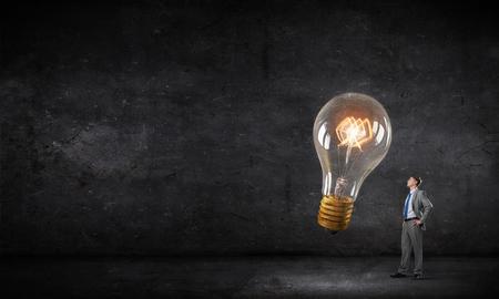 Jeune homme d'affaires dans l'obscurité regardant ampoule incandescent