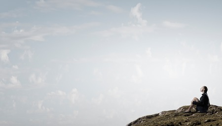 incapacity: Thoughtful young businesswoman sitting alone on rock top Stock Photo