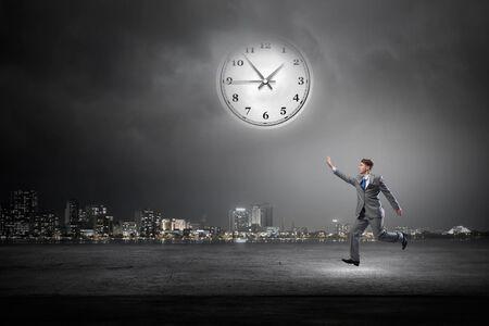 atrapar: Hombre de negocios corriendo y tratando de recuperar el tiempo Foto de archivo