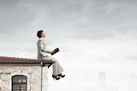 develope: Adult woman in suit with old book in hand sitting on roof Stock Photo