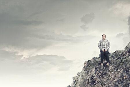 cerveza negra: Mujer robusta de mediana edad sentado en la cima de la roca