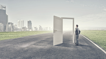 new opportunity: Businessman standing in front of opened doors and making decision Stock Photo