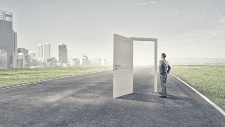 El hombre de negocios de pie delante de puertas abiertas y de toma de decisiones Foto de archivo