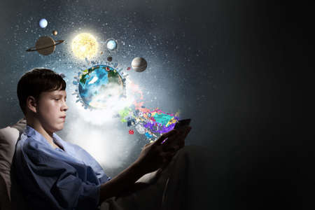 lying in: Teenage boy in pajamas lying in bed using tablet pc.  Stock Photo