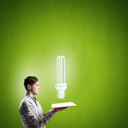 broaden: Young man with opened book and bulb on it on color background