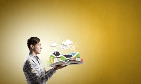 storytelling: Young student guy with opened book in hands