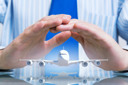 aviation: Hands of businessman and model of flying airplane