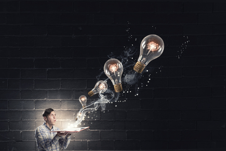 broaden: Young man holding opened book with glass glowing light bulbs flying out