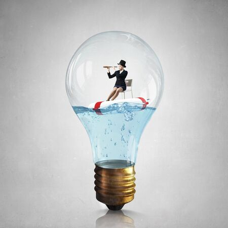 buoy: Young businesswoman floating on life buoy inside of light bulb
