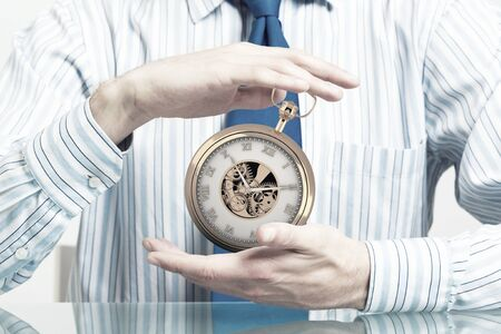punctuality: Hands of businessman holding with care time concept