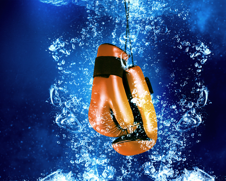 clear: Boxing gloves sinking in clear blue water