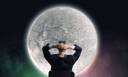 moon chair: Rear view of businessman sitting on chair with hands on head Stock Photo