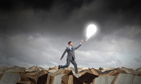 business ideas: Running young businessman trying to catch glowing light bulb