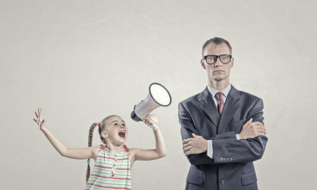 angry kid: Child screaming with megaphone to adult indifferent man Stock Photo