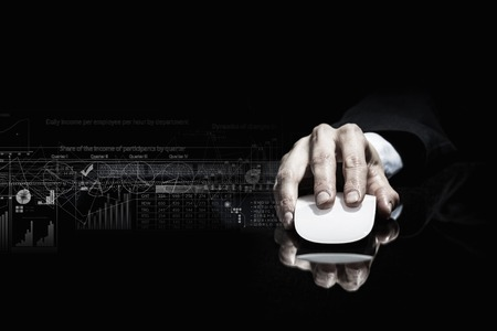 reflective background: Hand of businessman in suit on dark background using wireless computer mouse