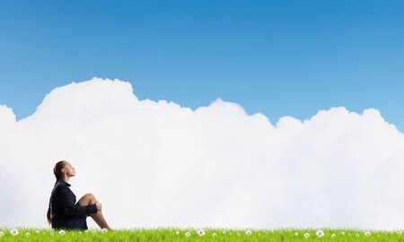 incapacity: Bored young businesswoman sitting alone on green grass