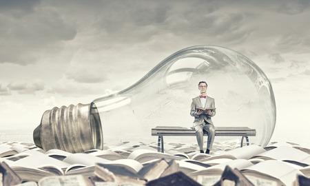 Jeune homme d'affaires à l'intérieur de la lumière ampoule livre de lecture Banque d'images - 48063058
