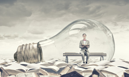 human mind: Young businessman inside of light bulb reading book