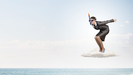 risky job: Young businesswoman in suit and diving mask jumping in water Stock Photo