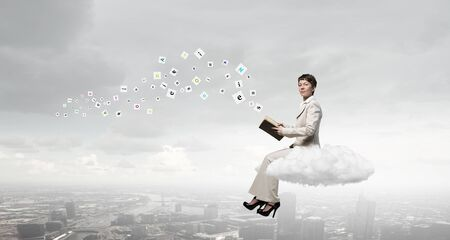 develope: Adult woman in suit with old book in hand sitting on cloud