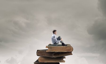 alone man: Young businessman sitting alone on pile of old books