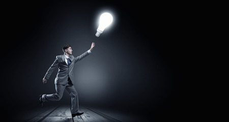 triumphant: Young businessman running and catching glowing light bulb