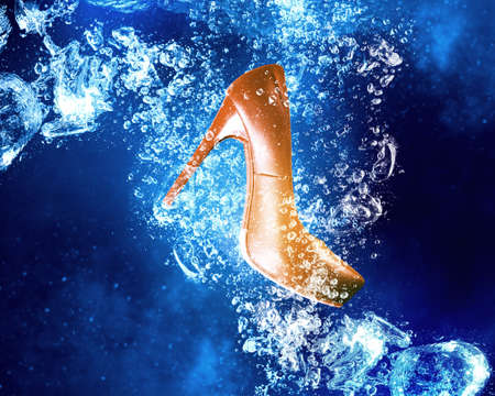 clear: Heeled shoe sinking in clear blue water Stock Photo