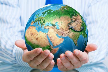 商人手中拿著地球的行星。這一形象的元素是由美國航空航天局提供 版權商用圖片