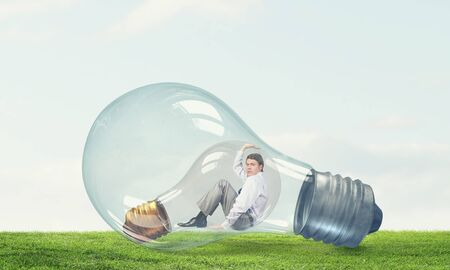 trapped: Young thoughtful businessman trapped inside of light bulb