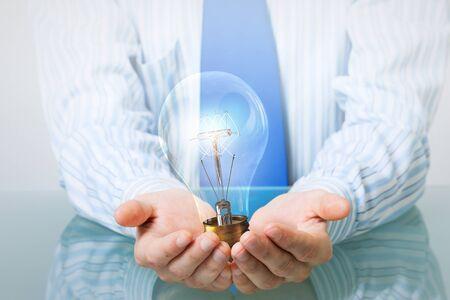 ahorro energia: Las manos del hombre de negocios que llevan a cabo con la bombilla de cristal cuidado Foto de archivo