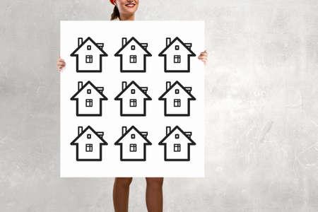 unrecognizable: Unrecognizable woman holding placard with house symbol