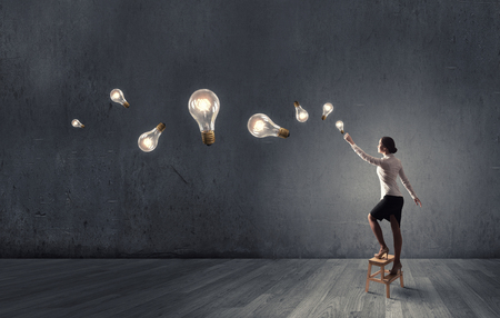business ideas: Back view of businesswoman standing on chair and reaching light bulb