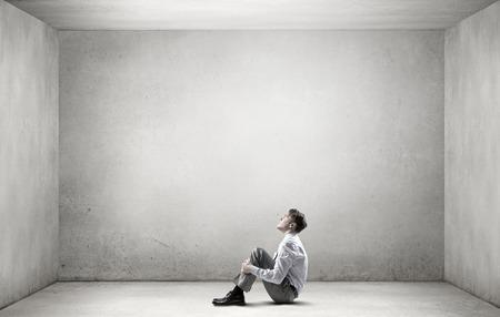 Homem de negócios deprimido novo sentada no chão, sozinho no quarto vazio
