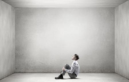 Jeune homme d'affaires déprimé assis sur le plancher seul dans salle vide