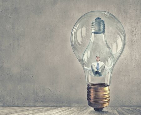 are trapped: Young businessman trapped inside of light bulb and calling for help