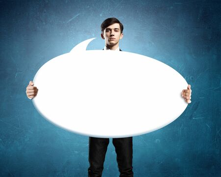 text bubble: Young businessman showing blank white speech banner. Place for text