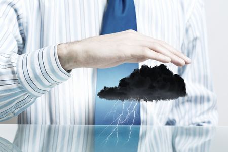 privat: Hand of businessman protecting black raining cloud