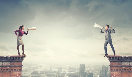 Young businessman and businesswoman on building top screaming on each other in paper trumpets