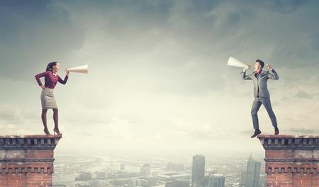 personas comunicandose: Joven empresario y empresaria en el edificio de la parte superior gritando el uno al otro en las trompetas de papel