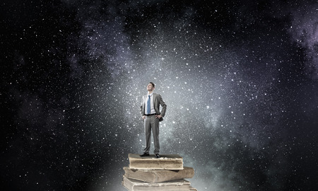 broaden: Young confident businessman with arms on waist standing on pile of old books