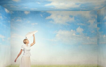 the carefree: Young carefree woman with paper plane in hands Stock Photo