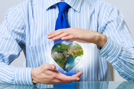 hands holding heart: Businessman hands holding heart shaped Earth planet.