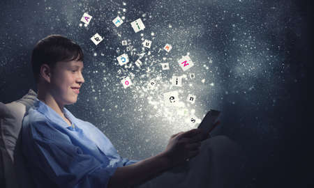 sleeping tablets: Teenage boy in pajamas lying in bed using tablet pc Stock Photo