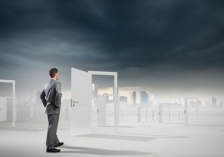 finding: Businessman standing in front of opened doors and making decision Stock Photo