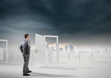 conclusion: El hombre de negocios de pie delante de puertas abiertas y de toma de decisiones Foto de archivo