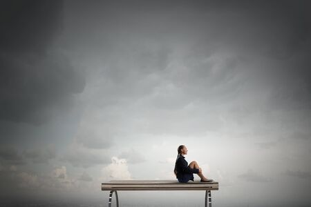 incapacity: Bored young businesswoman sitting alone on wooden bench Stock Photo