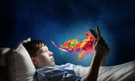 lying in: Teenage boy in pajamas lying in bed using tablet pc Stock Photo