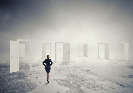 new entry: Businesswoman standing in front of opened doors and making decision