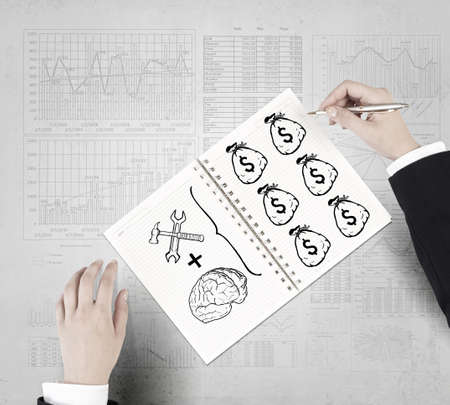 making: Businessman hands drawing money making formula in notepad Stock Photo